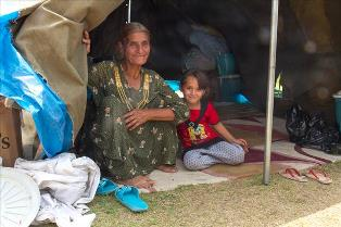 Iraqi_grandmother_and_granddaughter_in_refugge_tent_small